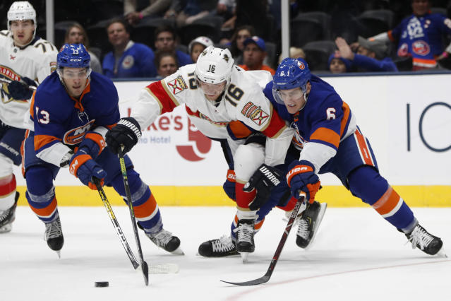 New York Islanders center Mathew Barzal (13) and defenseman Ryan Pulock (6) defend against Florida Panthers center Aleksander Barkov (16) during the first period of an NHL hockey game Saturday, Oct. 12, 2019, in Uniondale, N.Y. (AP Photo/Kathy Willens)