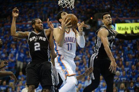 May 12, 2016; Oklahoma City, OK, USA; Oklahoma City Thunder center Enes Kanter (11) drives to the basket between San Antonio Spurs forward Kawhi Leonard (2) and guard Danny Green (14) during the third quarter in game six of the second round of the NBA Playoffs at Chesapeake Energy Arena. Mandatory Credit: Mark D. Smith-USA TODAY Sports / Reuters