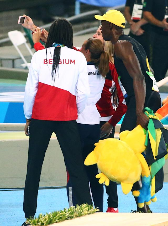 2016 Rio Olympics - Athletics - Final - Men's 100m Final - Olympic Stadium - Rio de Janeiro, Brazil 14/08/2016. Usain Bolt (JAM) of Jamaica poses for a selfie with heptathletes Jessica Ennis-Hill (GBR) of Britain, Brianne Theisen-Eaton (CAN) of Canada and Nafissatou Thiam (BEL) of Belgium REUTERS/David Gray FOR EDITORIAL USE ONLY. NOT FOR SALE FOR MARKETING OR ADVERTISING CAMPAIGNS.