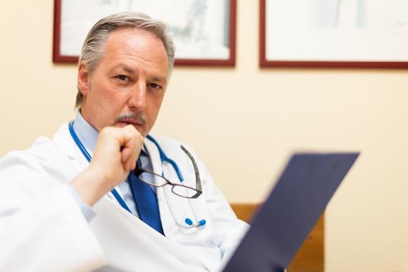 A doctor in deep thought, holding a clipboard.