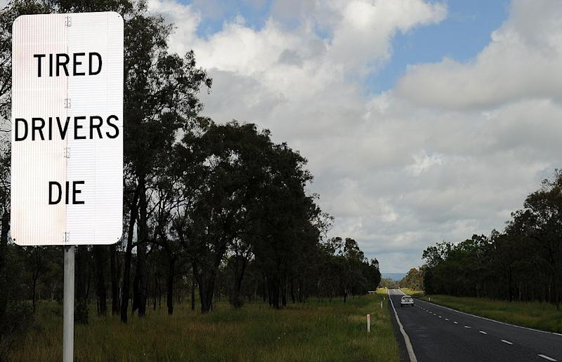 "A roadside sign on the Bruce Highway, Mackay reads ""tired drivers die""."