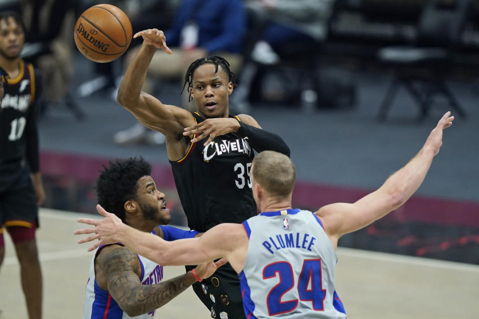 Cleveland Cavaliers' Isaac Okoro (35) passes against Detroit Pistons' Mason Plumlee (24) and Detroit Pistons' Saddiq Bey (41) in the first half of an NBA basketball game, Wednesday, Jan. 27, 2021, in Cleveland. (AP Photo/Tony Dejak)