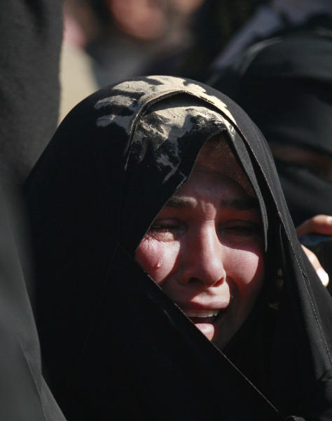 A Shiite woman weeps as she covers her head with mud as a sign of grief for Imam Hussein during the Muslim festival of Arbaeen in Karbala, 50 miles (80 kilometers) south of Baghdad, Iraq, Thursday, Jan. 3 , 2013. The holiday marks the end of the forty day mourning period after the anniversary of the 7th century martyrdom of Imam Hussein, the Prophet Muhammad's grandson. (AP Photo/Hadi Mizban)