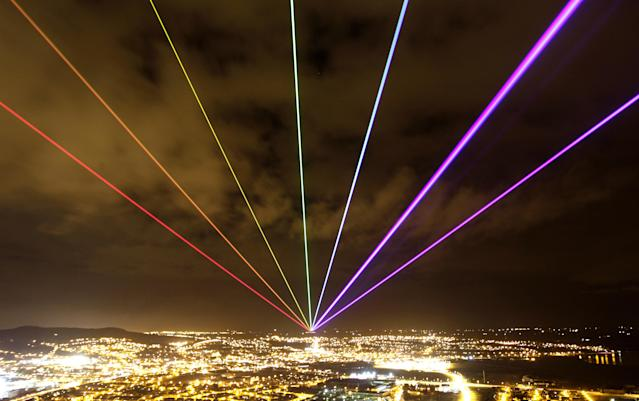 The Global Rainbow is projected into the night sky from Scrabo Tower, Newtownards, Northern Ireland, Friday, March 16, 2012. The large scale outdoor laser projection created by New York artist Yvette Mattern is visible across the night sky, the event signals 100 days to go until the opening of the London 2012 Festival which is a tweleve-week festival of arts running parallel to the Olympic Games taking place in London. (AP Photo/Peter Morrison)