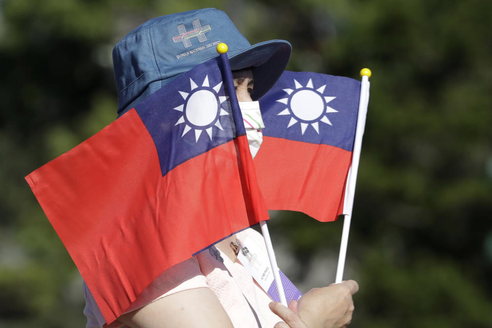 FILE - In this Sunday, Oct. 10, 2021, file photo, a woman holds up Taiwan national flags during National Day celebrations in front of the Presidential Building in Taipei, Taiwan. China says a recent increase in military exercises and warplane missions near Taiwan are necessary to defend national sovereignty and territorial integrity. (AP Photo/Chiang Ying-ying, File)