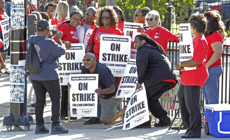 Chicago public school teachers take a group picture as they walk a picket line outside Shoop Elementary School in Chicago, Tuesday, Sept. 11, 2012, on the second day of a strike in the nation's third-largest school district as negotiations by the two sides failed to reach an agreement Monday in a bitter contract dispute over evaluations and job security. (AP Photo/M. Spencer Green)