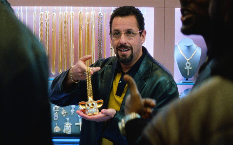 """This image released by A24 shows Adam Sandler in a scene from """"Uncut Gems."""" The Safdie brothers' Diamond District crime film """"Uncut Gems"""" and Robert Eggers' fever-dream period tale """"The Lighthouse"""" lead the 35th annual Film Independent Spirit Awards with five nominations each. The Spirit Awards will be held Feb. 8, the day before the Academy Awards.  (A24 via AP)"""