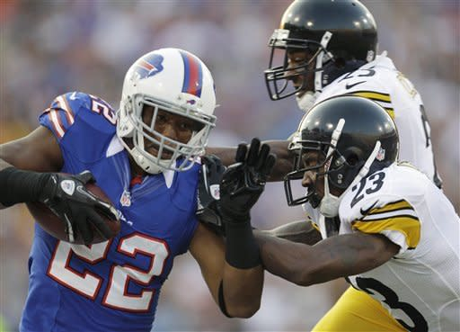 Buffalo Bills' Fred Jackson (22) runs under pressure from Pittsburgh Steelers' Keenan Lewis (23) and Ryan Clark (25) during the first quarter of a preseason NFL football game in Orchard Park, N.Y., Saturday, Aug. 25, 2012. (AP Photo/Gary Wiepert)