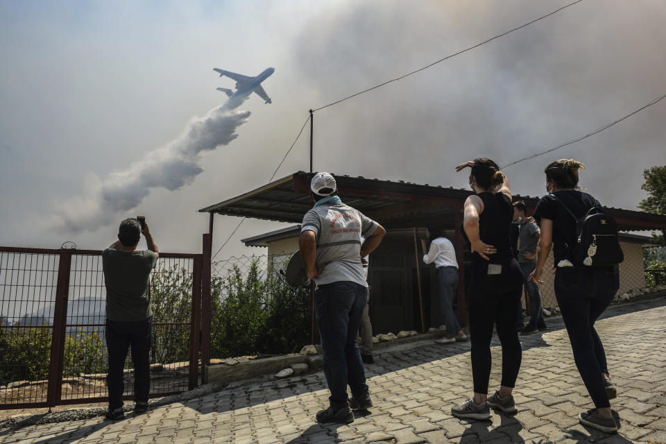 A plane pours water over the fire-devastating Sirtkoy village, near Manavgat, Antalya, Turkey, Sunday, Aug. 1, 2021. More than 100 wildfires have been brought under control in Turkey, according to officials. The forestry minister tweeted that five fires are continuing in the tourist destinations of Antalya and Mugla. (AP Photo)