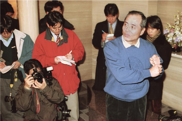 In this Dec. 11, 1998, photo, then Fukuoka Daiei Hawks manager Sadahara Oh, front right, answers to reporters' questions in front of his house in Fukuoka, southern Japan, following the Japanese baseball team's investigation report on suspicion of sign stealing. If you thought the use of technology to steal catchers' signs was only a problem for Major League Baseball and the Houston Astros, or something new. Japan went through a similar scandal just over 20 years ago. In a widely reported scandal in 1998, a camera in the Fukuoka Dome was discovered to be focused on the catcher. Officials of the Hawks - now the SoftBank Hawks - reportedly monitored the signs and relayed them by walkie-talkie to fans in the stands, who then used signals to batters to indicated the next pitch. (Kyodo News via AP)