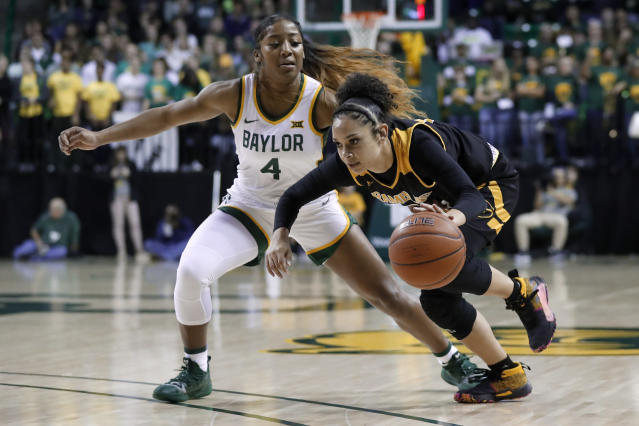 Baylor guard Te'a Cooper (4) defends as Grambling State guard Candice Parramore (15) drives to thee basket in the first half of an NCAA college basketball game in Waco, Texas, Friday, Nov. 8, 2019. (AP Photo/Tony Gutierrez)