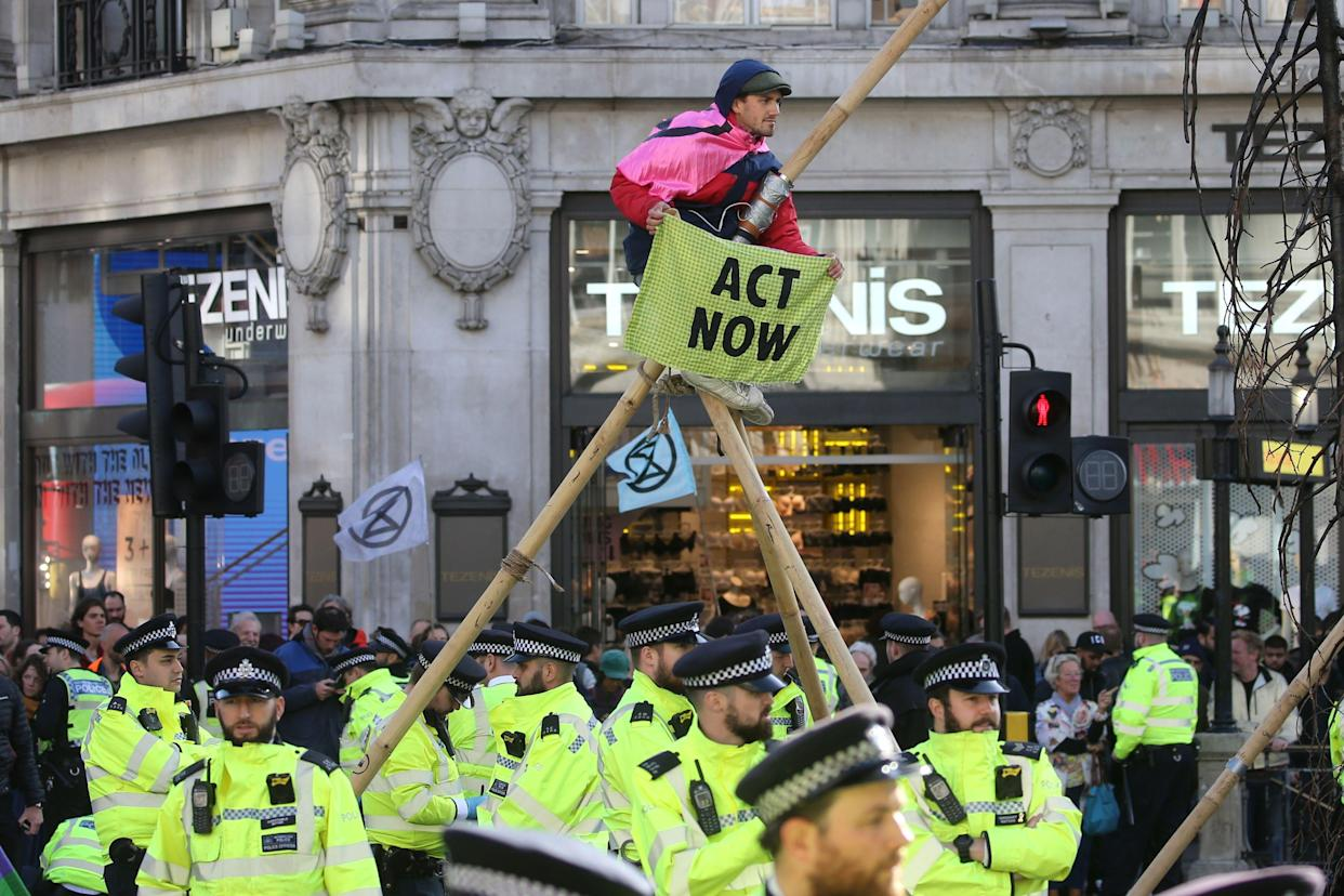 Police monitor as a climate activist perches on a make-shift structure in Oxford Street during the twelfth day of demonstrations by the climate change action group Extinction Rebellion, in London, on October 18, 2019. - The Extinction Rebellion pressure group has been staging 10 days of colourful but disruptive action across London and other global cities to draw attention to climate change. (Photo by ISABEL INFANTES / AFP) (Photo by ISABEL INFANTES/AFP via Getty Images)