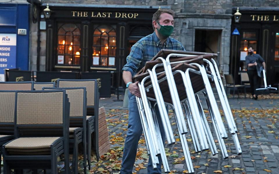 A man stacks away chairs outside The last Drop pub as it closes in The Grassmarket, Edinburgh - Andrew Milligan/PA
