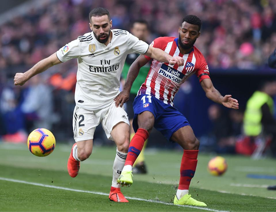 MADRID, SPAIN: Dani Carvajal of Real Madrid tackles Thomas Lemar of Atleti (Photo by Denis Doyle/Getty Images)