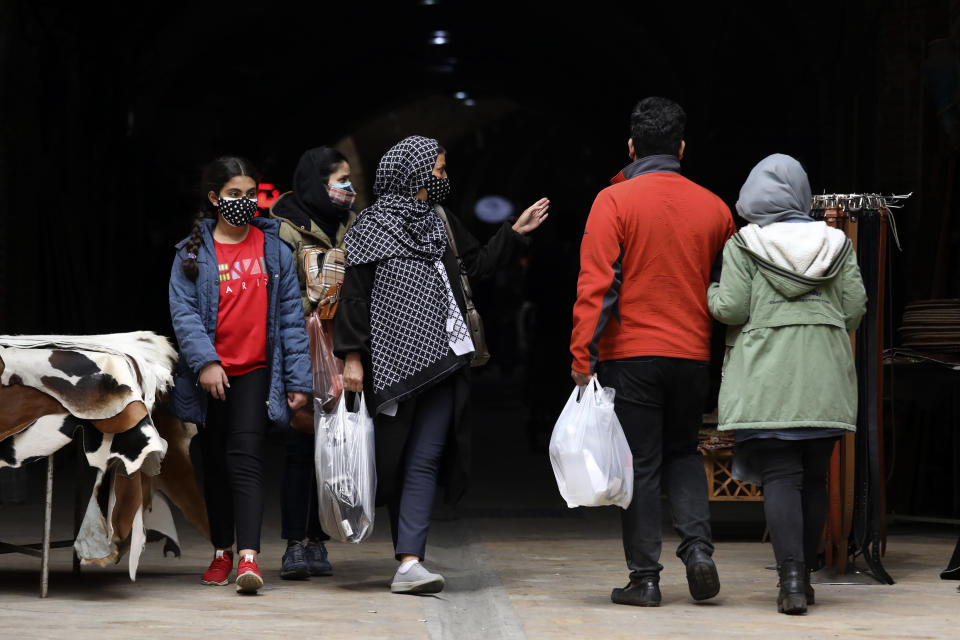 """Mask-clad shoppers walk at Tehran's Grand Bazaar, ahead of the Persian New Year, or Nowruz, meaning """"New Day"""" in Iran, Monday, March 15, 2021. (AP Photo/Vahid Salemi)"""