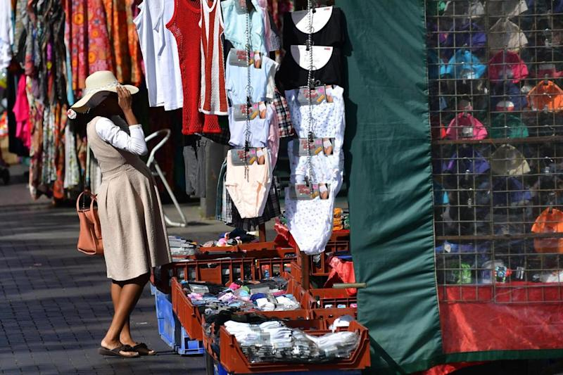 Walthamstow also made the top 10: A woman tries on a hat at the market on the high street (Getty Images)