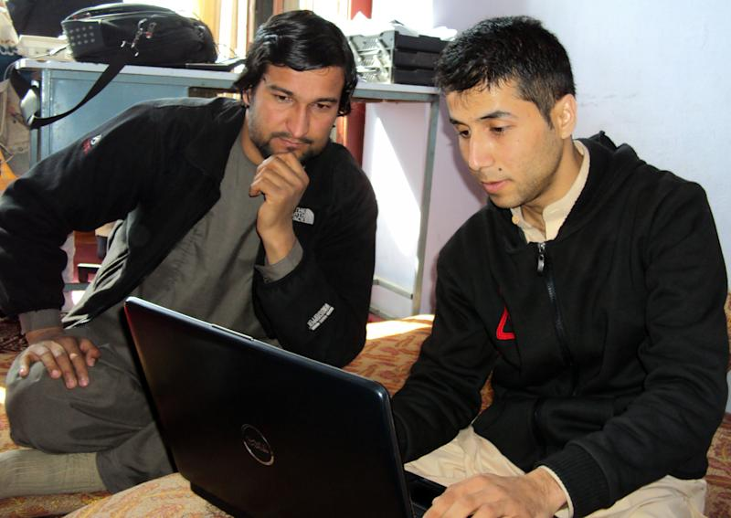 In this picture taken on Sunday, March 2, 2014, Afghan ex-translators for German military Shamsuddin Nawazish, left, and Walid Shirzad look at a laptop's screen during an interview with The Associated Press in Kunduz city, Afghanistan. According to the German government, about 950 Afghans have worked for Germany during the time its personnel have been present in Afghanistan, including drivers, translators and others. (AP Photo/Amad Yama)