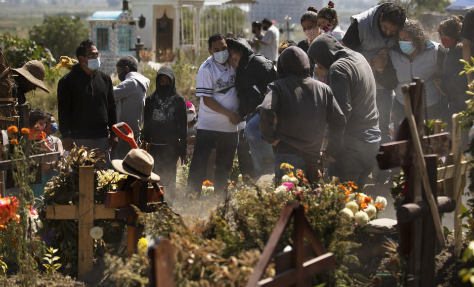"Relatives bury Isaac Nolasc,o who died of reasons not believed related to COVID-19, in a section of the municipal cemetery of Valle de Chalco amid the new coronavirus pandemic, on the outskirts of Mexico City, Sunday, Oct. 25, 2020. Mexican families traditionally flock to local cemeteries to honor their dead relatives as part of the ""Dia de los Muertos,"" or Day of the Dead celebrations, but according to authorities, the cemeteries will be closed this year to help curb the spread of COVID-19. (AP Photo/Marco Ugarte)"