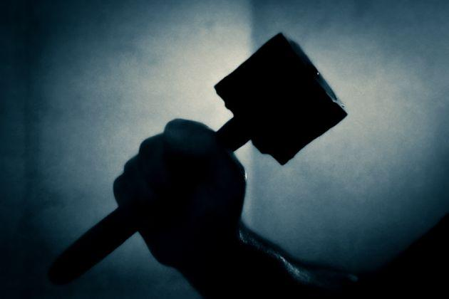 male arm holding a hammer on a silver blue background