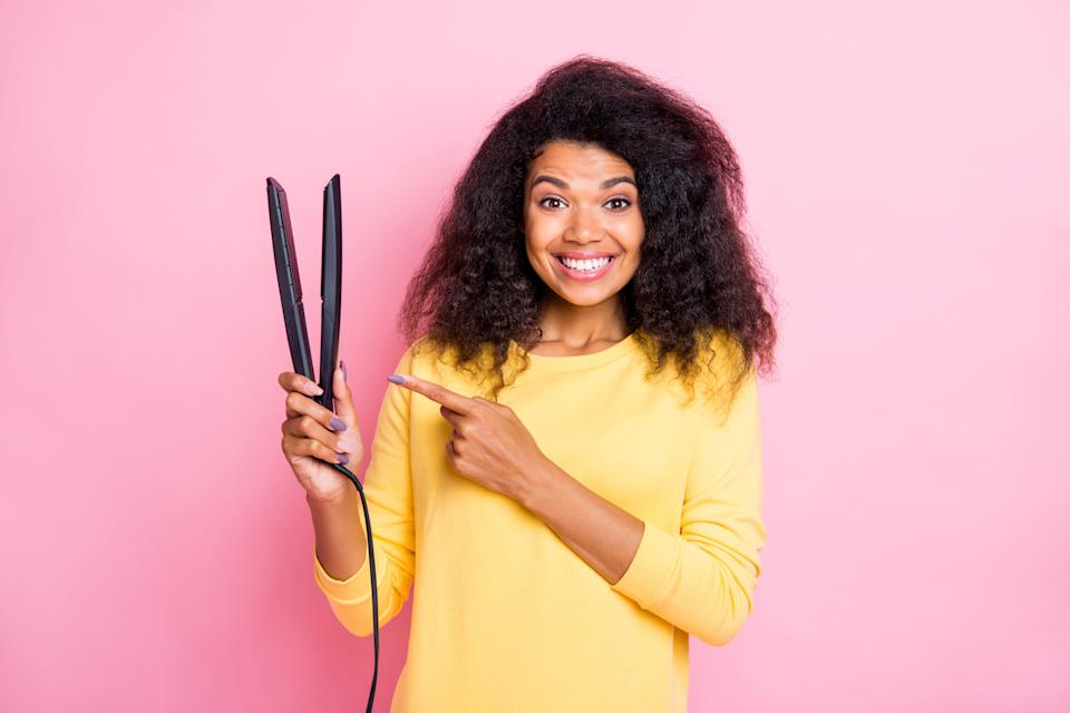 Portrait of funky positive lady holding a hair straightener