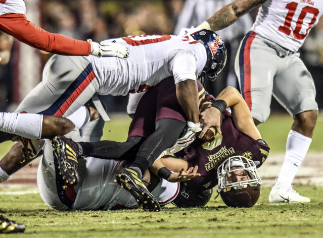 Mississippi State quarterback Garrett Shrader (6) is sacked by Mississippi defensive lineman Benito Jones (95) and defensive tackle Josiah Coatney (40) during an NCAA college football game in Starkville, Miss., Thursday, Nov. 28, 2019. (Bruce Newman/The Oxford Eagle via AP)