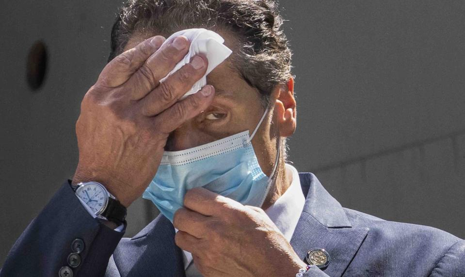FILE - This photo from Monday, Aug. 3, 2020, shows New York Gov. Andrew Cuomo wiping sweat from his face during a ceremony at the St. Nicholas Greek Orthodox Church at the World Trade Center in New York. Facing unprecedented political isolation, New York Gov. Andrew Cuomo is insisting he won't step down after allegations of sexual harassment. (AP Photo/Mark Lennihan, File)