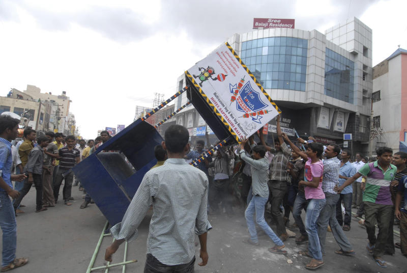 """FILE - In this July 31, 2013 file photo, anti-Telangana protesters vandalize a traffic policeman's platform after India's ruling coalition endorsed the creation of a new state """"Telangana"""" in Ananthapur in Andhra Pradesh state, India. Ever since India's ruling coalition endorsed the creation of the new southern state of Telangana, a rash of demands for new states have burst into mutinous life across India, with strikes and protests that could redraw the country's political map. Leaders of the Gorkhaland and Bodo movements, two of the most prominent splinter groups, view the Telangana decision as nothing short of a betrayal of their own dreams. (AP Photo/File)"""