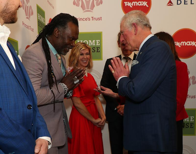 The Prince of Wales greets Levi Roots with a Namaste gesture as he arrives at the annual Prince's Trust Awards 2020 held at the London Palladium.
