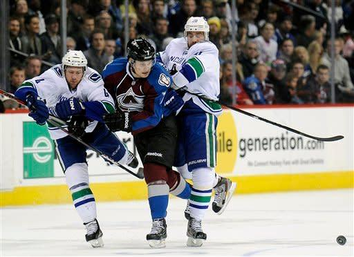 Vancouver Canucks defenseman Keith Ballard, left, and left wing Chris Higgins, right, fight for the puck against Colorado Avalanche center John Mitchell, center, in the first period of an NHL hockey game on Sunday, March 24, 2013, in Denver. (AP Photo/Chris Schneider)