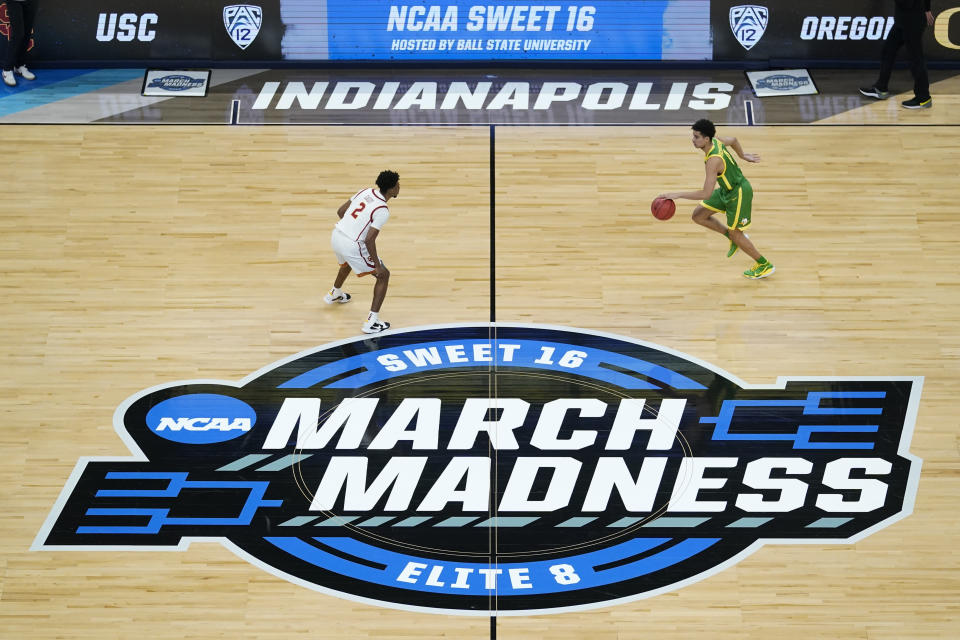 FILE - Oregon guard Will Richardson, right, drives up court in front of Southern California guard Tahj Eaddy (2) during the first half of a Sweet 16 game in the NCAA men's college basketball tournament at Bankers Life Fieldhouse in Indianapolis, in this Sunday, March 28, 2021, file photo. Arena branding was among the differences people noticed between the NCAA's two biggest events, the women's and men's basketball tournaments. (AP Photo/Darron Cummings, File)