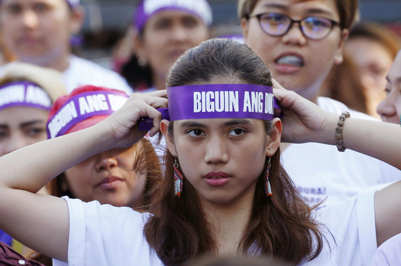 """FILE - In this March 8, 2018, file photo, a protester adjusts her headband reading """"Frustrate the dictatorship!"""" during a rally at a Manila square to mark International Women's Day which largely turns out to be an anti-government event in Manila, Philippines. The Philippine president signed Tuesday, July 16, 2019 a bill into law penalizing a range of acts of sexual harassment including catcalling, wolf-whistling and persistent telling of sexual jokes, which pro-women's groups have accused him of committing. (AP Photo/Bullit Marquez, File)"""