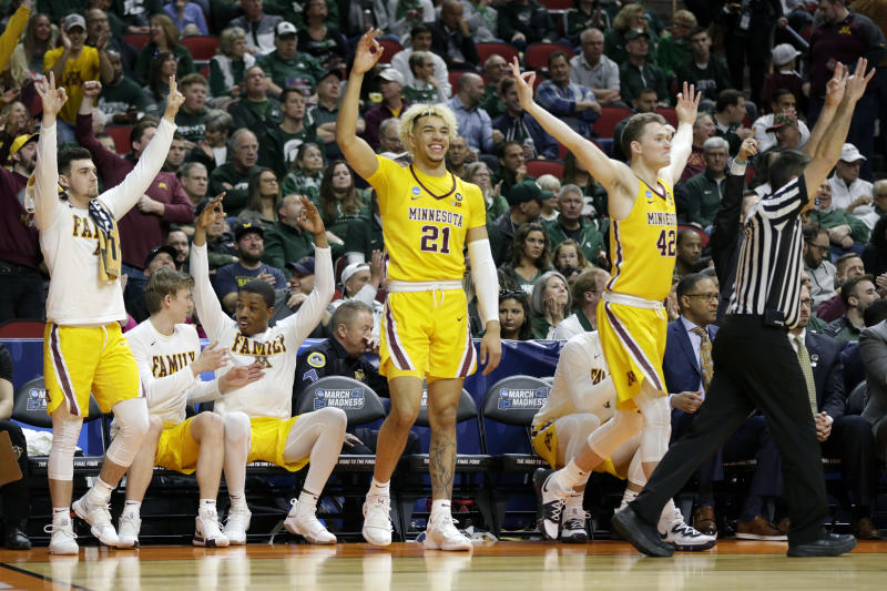 The Minnesota bench celebrates a three-point basket during the second half of a first round men's college basketball game against Louisville in the NCAA Tournament, in Des Moines, Iowa, Thursday, March 21, 2019. (AP Photo/Nati Harnik)