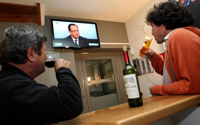 French people watch a live broadcast television debate with French President Francois Hollande, in a bar in a village of La Bastide Clairence, southwestern France, Thursday, March 28, 2013. (AP Photo/Bob Edme)