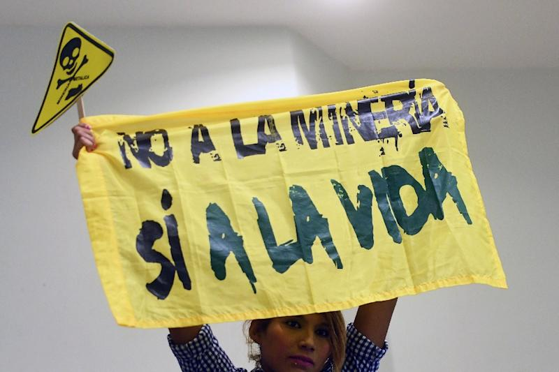 """A woman holds a banner reading """"No to mining. Yes to life"""" during a protest against mining at the Legislative Assembly in San Salvador on March 29, 2017"""