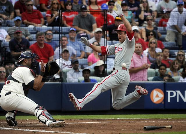 Philadelphia Phillies' Chase Utley, right, beats the throw to home to score as Atlanta Braves catcher Gerald Laird, left, defends the plate on a Kevin Frandsen single to center field during the fourth inning of a baseball game on Sunday, Sept. 29, 2013, in Atlanta. (AP Photo/John Amis)
