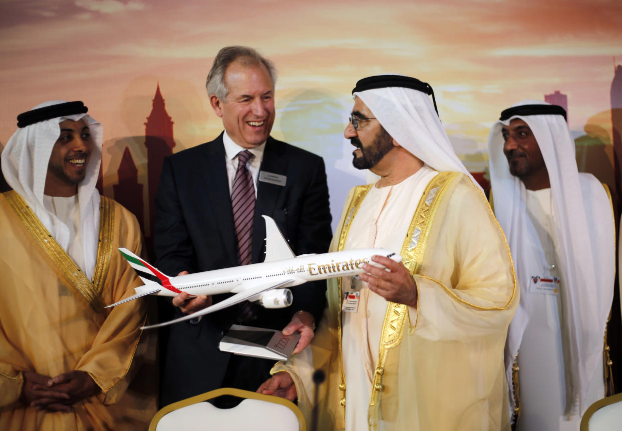 Boeing Chairman James McNerney (2nd L) shows United Arab Emirates' Prime Minister and Ruler of Dubai Sheikh Mohammed bin Rashid al-Maktoum (2nd R) a model of the new version of its 777 long-haul jet during the Dubai Airshow November 17, 2013. REUTERS/Ahmed Jadallah