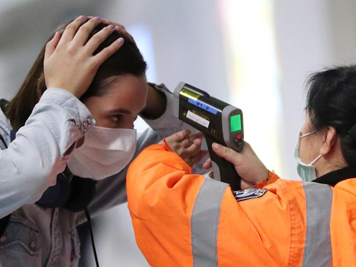 A worker checks the temperature of a passenger arriving into Hong Kong International Airport with an infrared thermometer, following the coronavirus outbreak in Hong Kong, China, February 7, 2020.