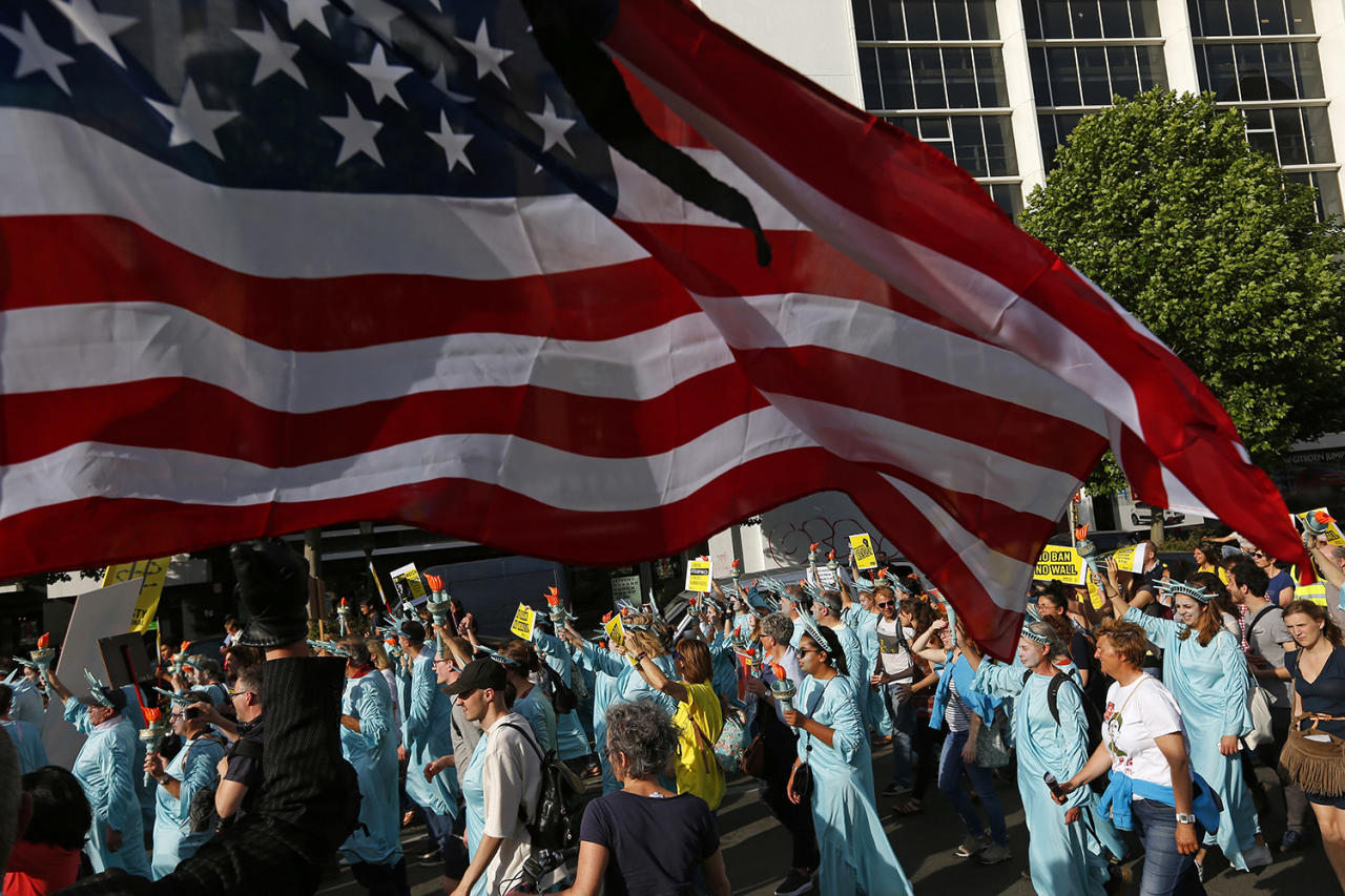 <p>Protesters dressed as the Statue of Liberty march under a US flag during a demonstration in the center of Brussels on May 24, 2017. Demonstrators marched in Brussels ahead of a visit of US President Donald Trump and a NATO heads of state summit which will take place on Thursday. (Photo: Peter Dejong/AP) </p>