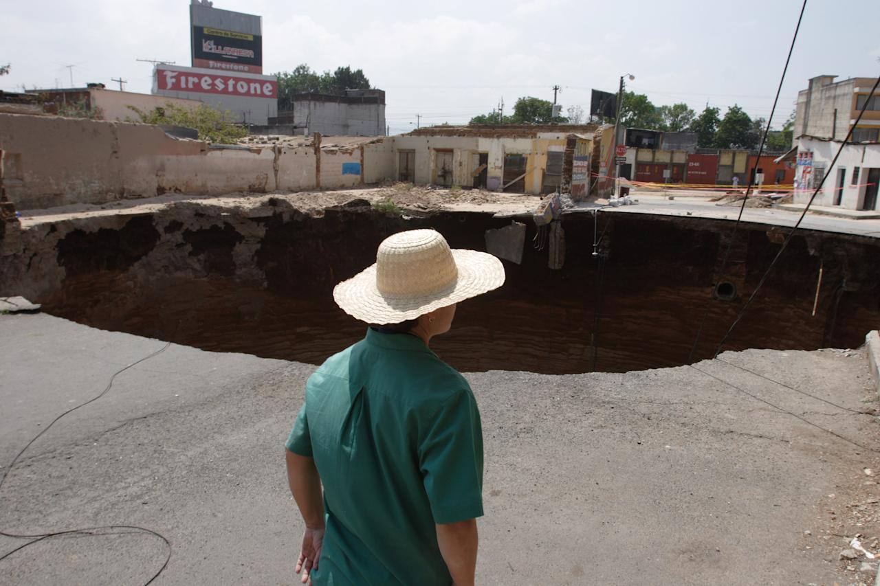 A woman observes a giant sinkhole in Guatemala City, Wednesday, Feb. 28, 2007. A 330-foot-deep sinkhole killed at least three people and swallowed about a dozen homes early Friday, forcing the evacuation of nearly 1,000 people in a crowded city neighborhood. (AP Photo/Alexandre Meneghini)