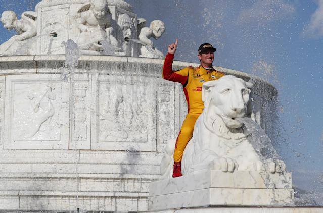 FILE - In this June 3, 2018, file photo, Ryan Hunter-Reay sits on a marble lion in the James Scott Memorial fountain after winning the second race of the IndyCar Detroit Grand Prix auto racing doubleheader in Detroit. His losing streak finally over, Hunter-Reay has bigger goals than simply winning a race. The 37-year-old Hunter-Reay had been running well this year, but his victory Sunday in Detroit was his first IndyCar win since 2015. It capped an impressive weekend that also included a second-place finish Saturday. He has six top-five finishes in eight races on the season, so perhaps it was only a matter of time before he ended the drought.( AP Photo/Carlos Osorio, File)