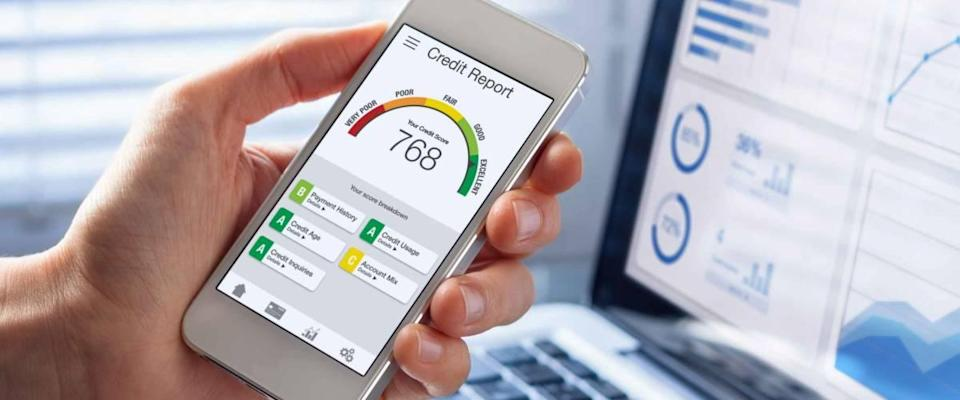 hand holding smartphone displaying credit score of 768, with computer in the background