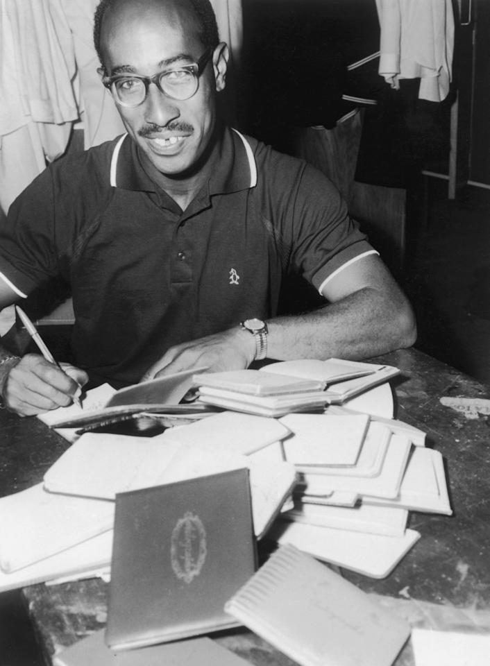 Jamaican bowler Alf Valentine catching up on his backlog of autographs after suffering from swollen hands caused by a food allergy, mid 1950's. (Photo by Central Press/Hulton Archive/Getty Images)