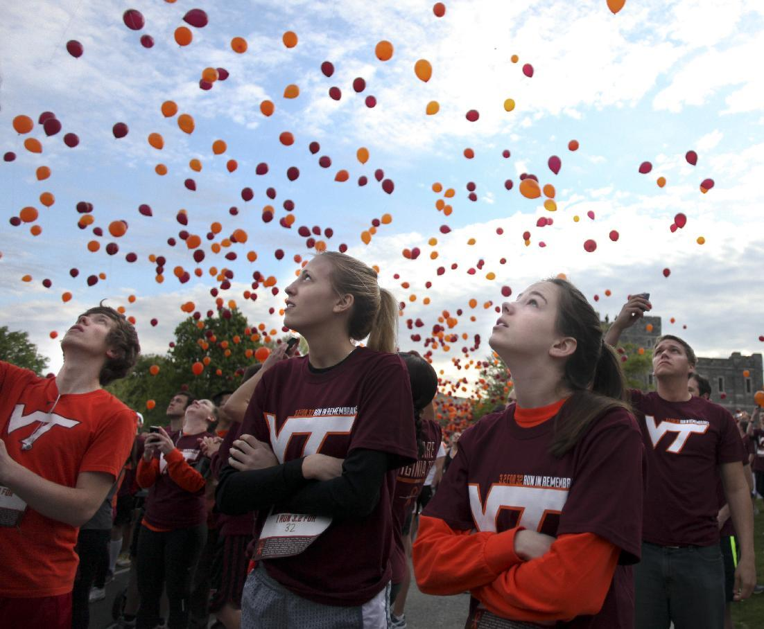 Paige Eckerd, right, and Kristy McCain, center, look skyward at released balloons at the start of a Run in Remembrance on the Virginia Tech campus in Blacksburg, Va. on Saturday, April 14, 2012. The 3.2-mile Run in Remembrance for the victims of the April 16, 2007, Virginia Tech shootings had about 6,500 participants registered in advance for the event in honor of the 32 killed in the deadliest mass shooting in modern U.S. history. (AP Photo/The Roanoke Times, Matt Gentry)