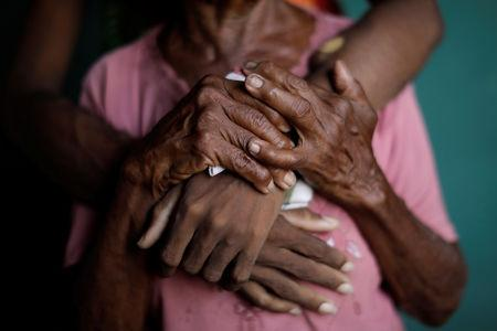 FILE PHOTO: The hands of Aidalis Guanipa, 25, a kidney disease patient, and her 83-year-old grandmother, are seen as they pose for a photo, while they wait for the electricity to return, at her house during a blackout, in La Concepcion, Venezuela, April 12, 2019. REUTERS/Ueslei Marcelino