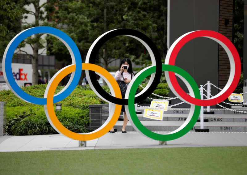FILE PHOTO: A woman wearing a protective mask amid the coronavirus disease (COVID-19) outbreak, takes a picture of the Olympic rings in front of the National Stadium in Tokyo