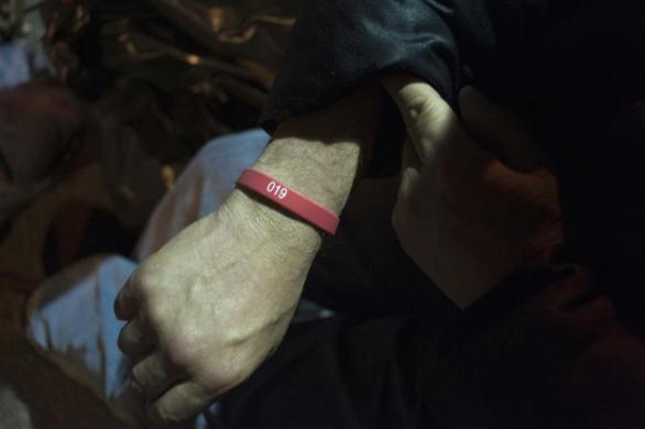 A job seeker displays the wristband he was given when he began queuing last week as he waits in front of the training offices of Local Union 46, a union representing metallic lathers and reinforcing ironworkers, in the Queens borough of New York, April 30, 2012.