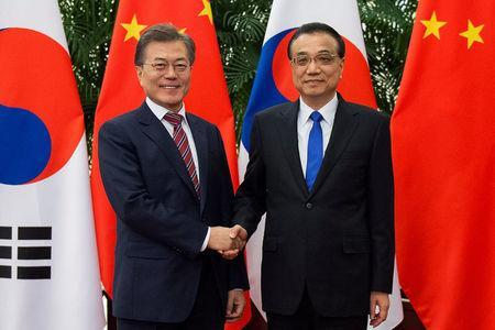South Korea's President Moon Jae-In (L) shakes hands with China's Premier Li Keqiang (R) at the Great Hall of the People in Beijing, China December 15, 2017. REUTERS/Nicolas Asfouri/Pool