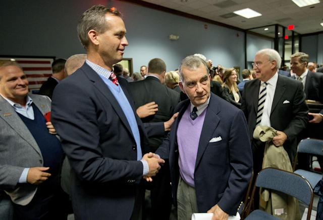 John Schuerholz, Atlanta Braves president, right, shakes hands with Derek Schiller, executive vice president of sales and marketing, as Cobb County officials approve a deal to build a new $672 million stadium for the team in the county at a commission hearing, Tuesday, Nov. 26, 2013, in Marietta, Ga. The Cobb County commissioners voted 4-1 Tuesday night to enter into a memorandum of understanding with the baseball team. Braves officials stunned local leaders earlier this month when they announced they would abandon Turner Field, a site just south of downtown Atlanta that has been their home since the team moved from Milwaukee in 1966. (AP Photo/David Goldman)