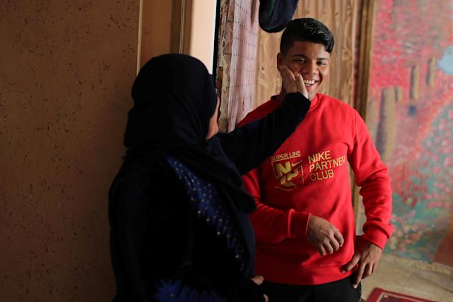 Palestinian Mustafa Sarhan, 19, a member of Gaza Skating Team, smiles as he is touched by his mother in their house in Gaza City March 18, 2019. Picture taken March 18, 2019. REUTERS/Mohammed Salem