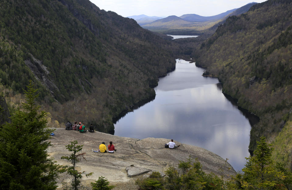 Hikers take in the view of Lower Ausable Lake from Indian Head Summit, Saturday, May 15, 2021, at the Adirondack Mountain Reserve near St. Huberts, N.Y. A free reservation system went online recently to control the growing number of visitors packing the parking lot and tramping on the trails through the private land of the Adirondack Mountain Reserve. The increasingly common requirements, in effect from Maui to Maine, offer a trade-off to visitors, sacrificing spontaneity and ease of access for benefits like guaranteed parking spots and more elbow room in the woods. (AP Photo/Julie Jacobson)